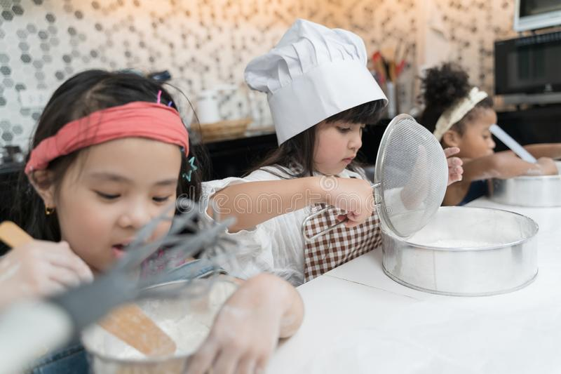 Group of kids are preparing the bakery in the kitchen .Children learning to cooking cookies. stock image