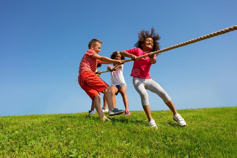 Happy kids pull rope cord - fun game in park lawn royalty free stock photo