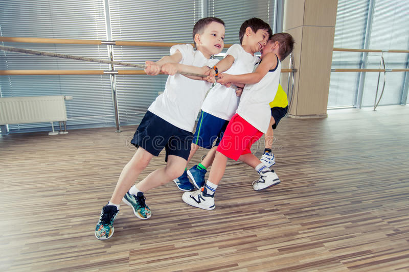 Group of kids pulling a rope in fitness room royalty free stock image