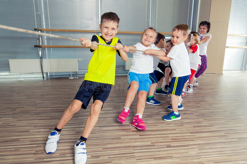 Group of kids pulling a rope in fitness room royalty free stock photos