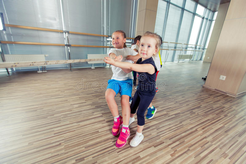 Group of kids pulling a rope in fitness room stock image