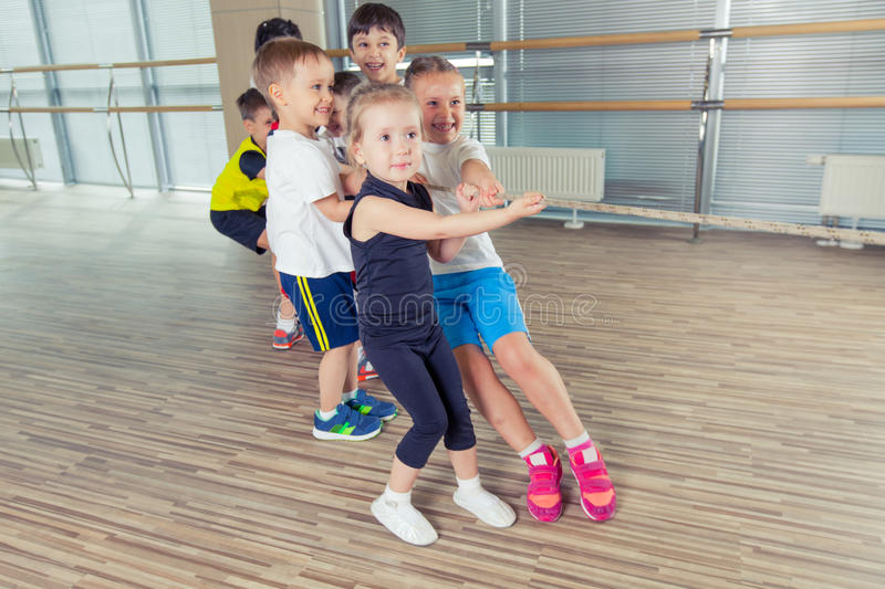 Group of kids pulling a rope in fitness room.  royalty free stock photo