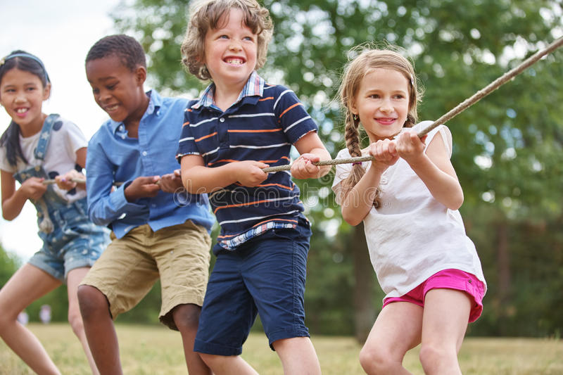 Group of kids pulling a rope stock photography