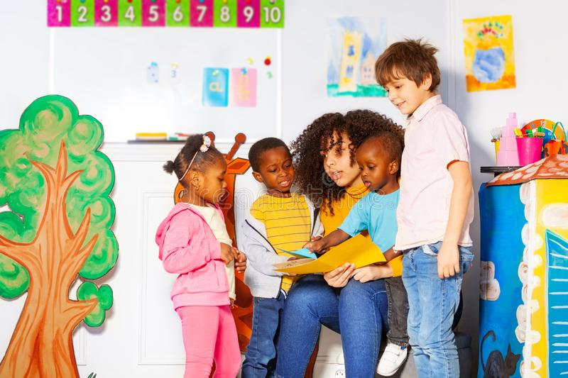 Group of kids reading book with teacher in nursery. Group of diverse looking kids reading book with teacher in nursery school class stock photos