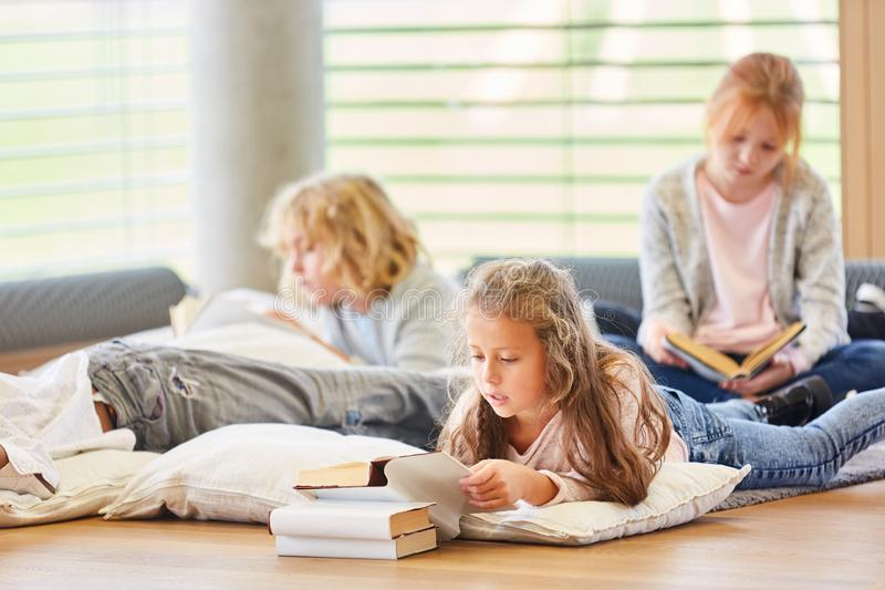 Group of kids are reading children`s books. Group of kids together read children`s books and storybooks stock image