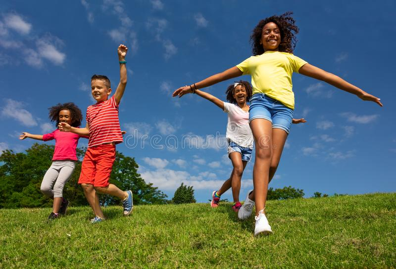 Group of kids run downhill with happy expression. Group of kids boy and girls run downhill with happy expression lifted hands smiling royalty free stock photo