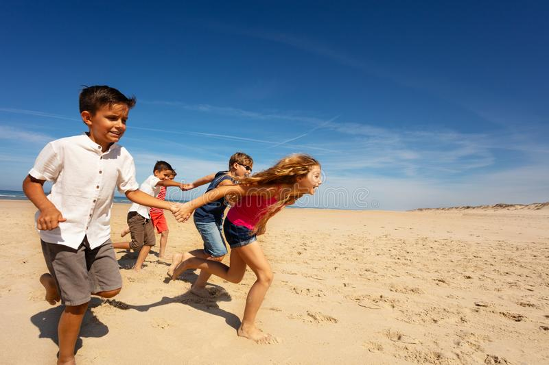 Group of kids run fast for fun on sea sand beach royalty free stock photo