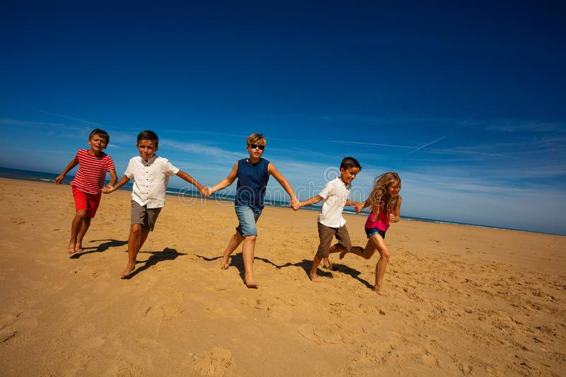 Group of kids run holding hands on the sand beach royalty free stock images