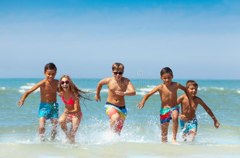 Group of kids running from the sea with splashes royalty free stock photography