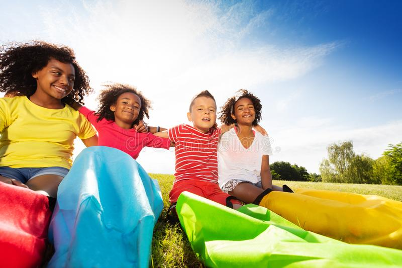 Group of kids sit with race sacks on the lawn royalty free stock photos