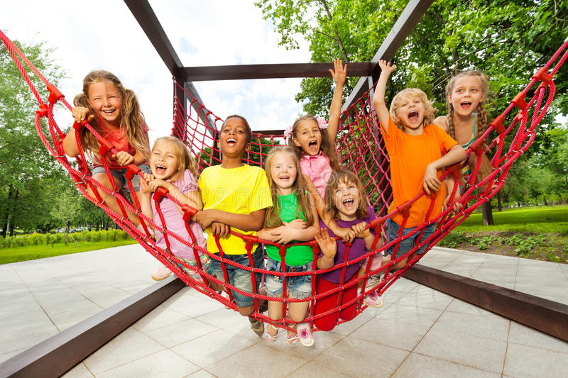 Group of kids sitting on playground net ropes. Together and net is hanging down royalty free stock photos
