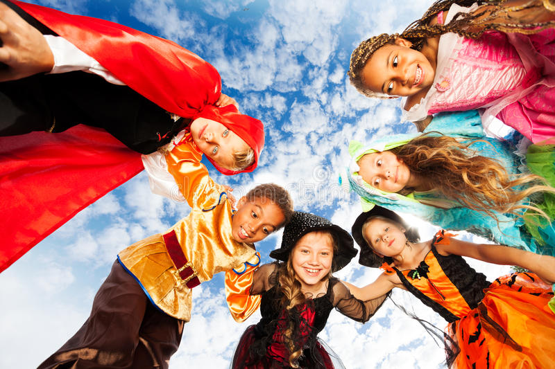 Group of kids wear Halloween costumes in circle. Group of happy kids standing in the circle together, friends boys and girls looking down with smile stock photography