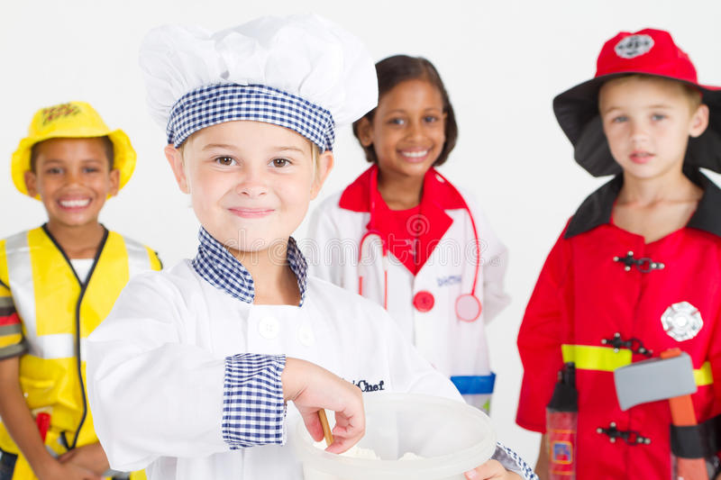 Group kids workers. Group of cute little kids play in various workers uniforms, studio shot, little girl as chef standing in front stock photography