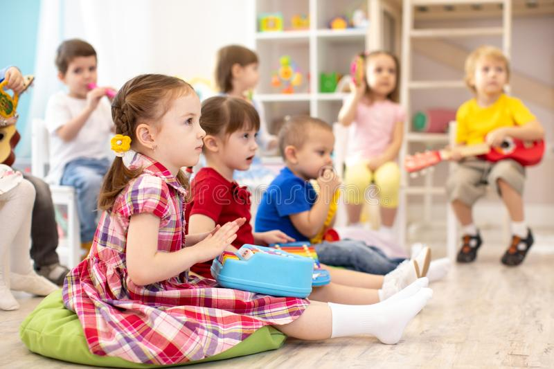 Group of kids 3-4 years old playing toy musical instruments. Early music education in kindergarten royalty free stock image