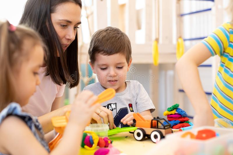 Group of kindergarten children playing with plasticine or dough at daycare. stock image