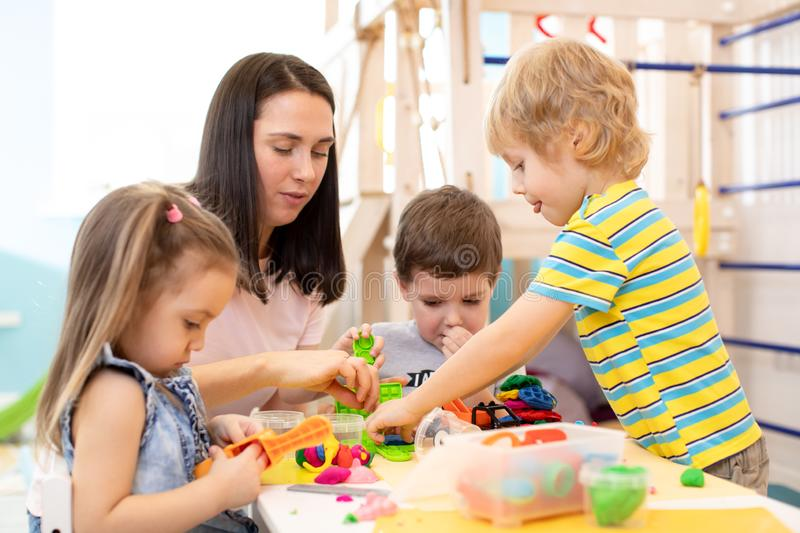 Group of kindergarten children playing with plasticine or dough. Little kids have a fun together with colorful modeling stock photo