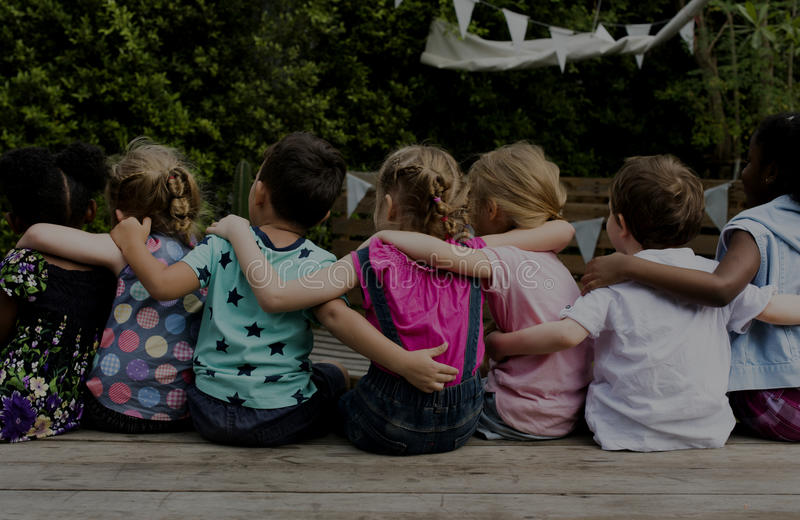 Group of kindergarten kids friends arm around sitting together stock images