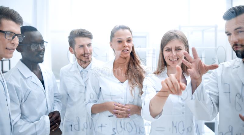 Group of laboratory scientists discussing their research in the. Group of concentrated colleagues in white coats discussing work in laboratory stock photography