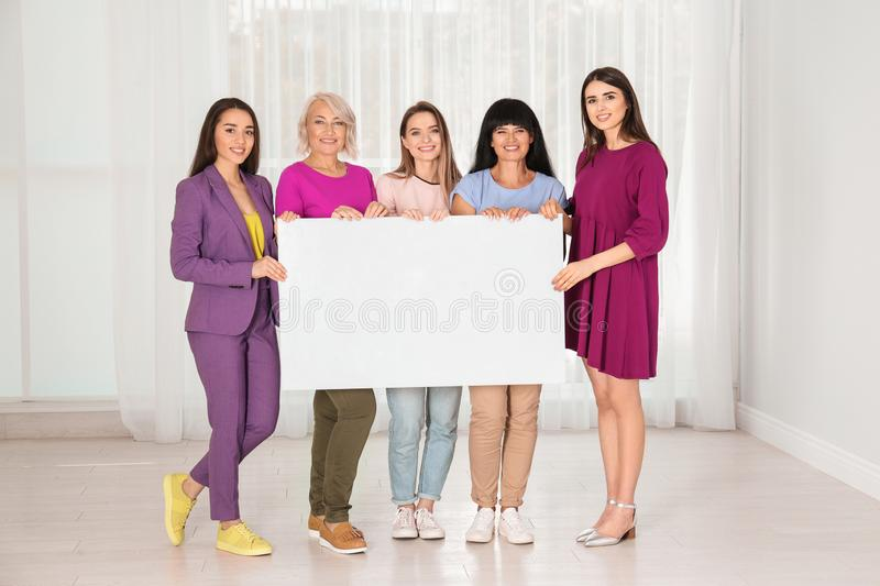 Group of ladies with empty poster near window, space for text. Women power concept stock photos