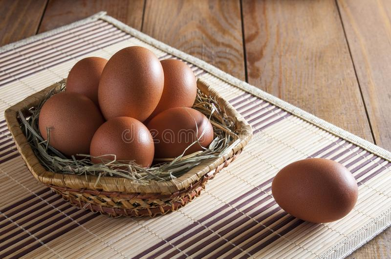 Group of large brown chicken eggs lies in a wicker basket and one lies next to the basket, on a wooden table.  royalty free stock photos
