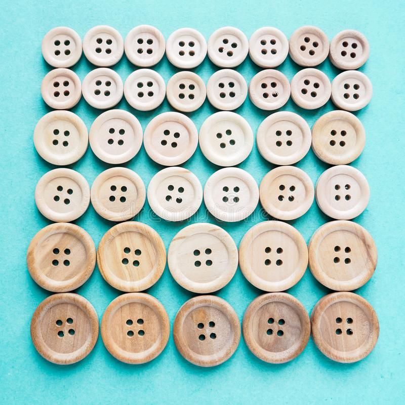 Group of large and small beige wooden buttons in row on blue background. Group of large and small beige wooden buttons in row on a blue background stock photography