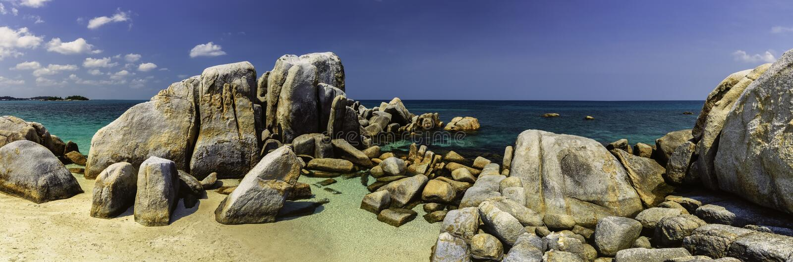 A group of large stones on the sea. Panoramic view of a group of large stones at sea stock image