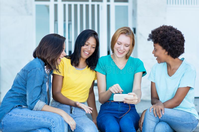 Group of latin and hispanic and african american female young adults watching movie clip at phone. Outdoor in summer in city royalty free stock photography