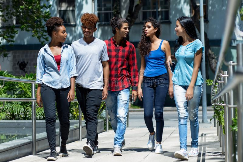Group of latin and hispanic and african american hipster young adults in city. Group of latin and hispanic and african american hipster young adults outdoors in stock image