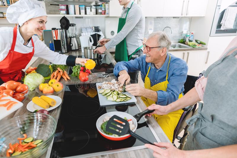 Group learning cooking in training kitchen with nutritionist stock images