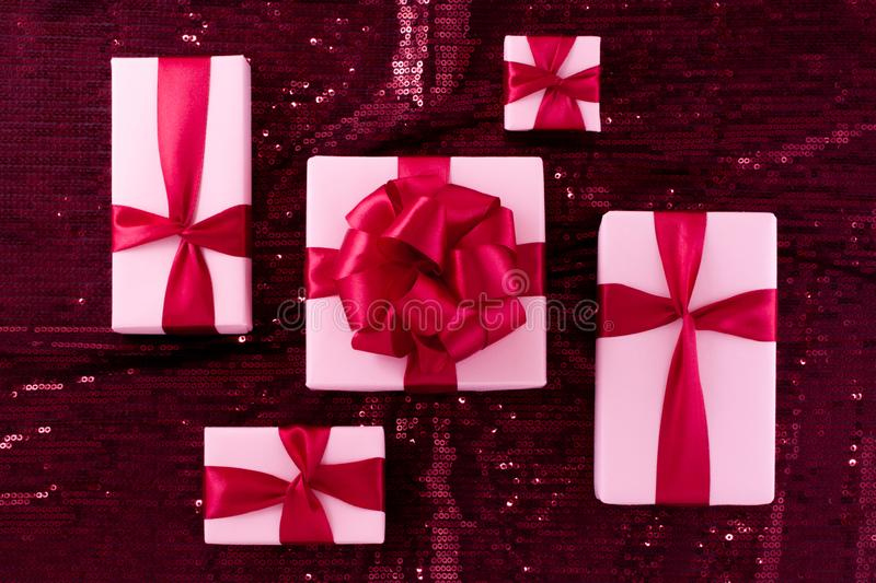 A group of light pastel pink boxes tied with a red satin ribbon with a bow of pop-pop. stock images