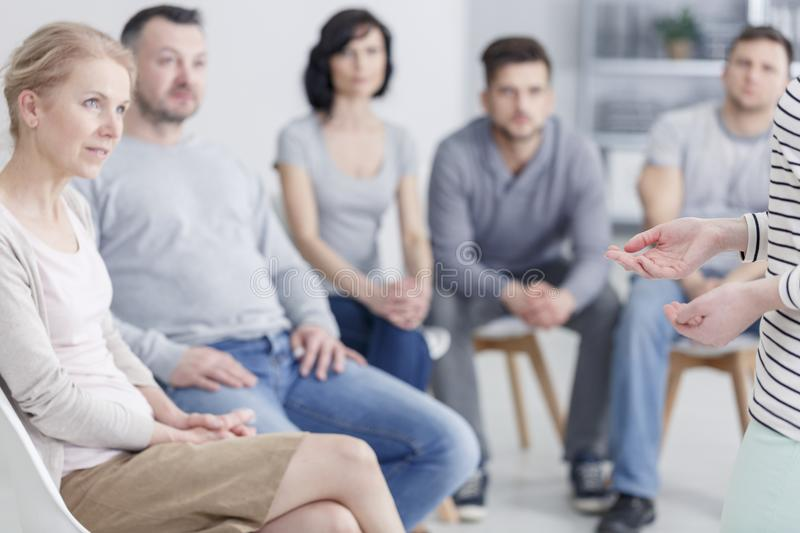 Group listening to woman. Group of people listening to a women sharing her story of drug addiction and rehab royalty free stock images