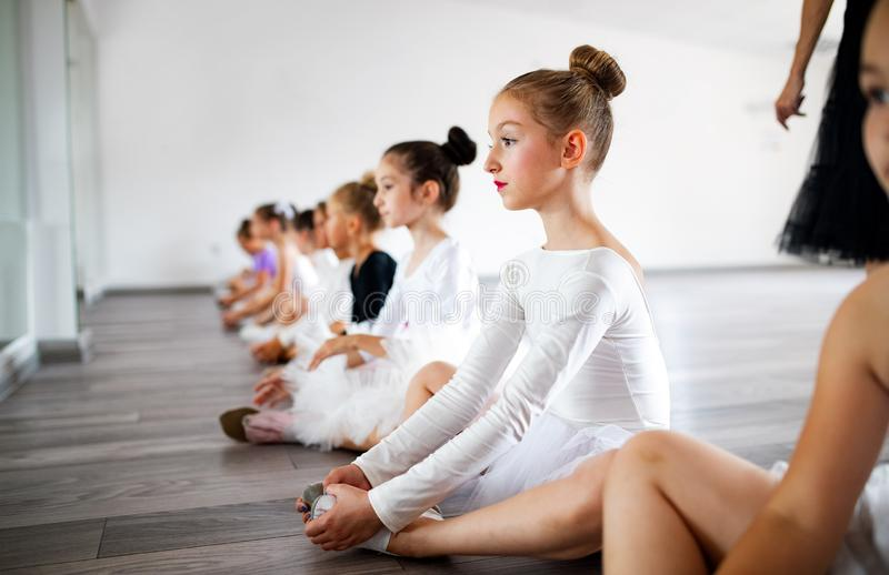 Group of little ballerinas girls doing exercises in dance school. Group of fit little ballerinas doing exercises in dance school royalty free stock photography