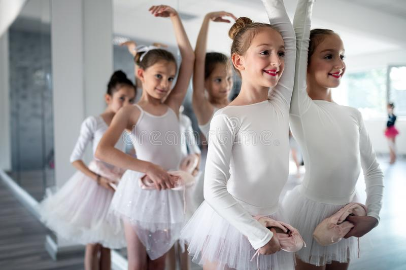 Group of little ballerinas girls doing exercises in dance school. Group of fit little ballerinas doing exercises in dance school royalty free stock images