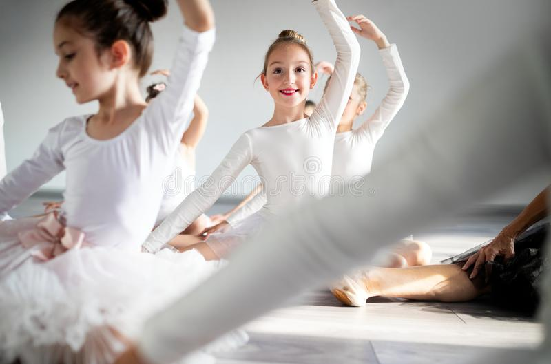 Group of little ballerinas girls doing exercises in dance school. Group of fit little ballerinas doing exercises in dance school stock images