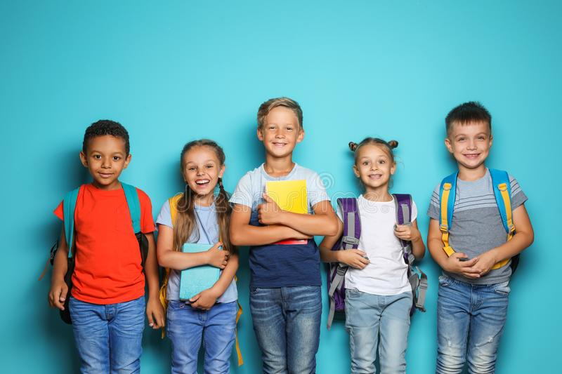 Group of little children with backpacks school supplies on color background royalty free stock photos