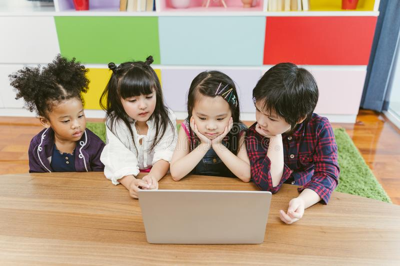 Group of little children diversity watching film together on laptop. Kids playing with laptop computer at home. stock photo