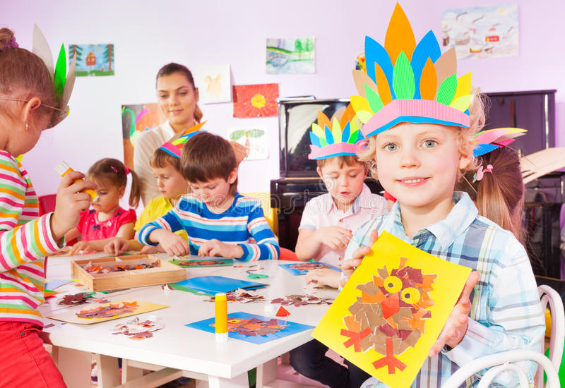 Group of little children glue and draw in class. Handsome blond boy sit with group of children by the table and show image with boys and girls glue with teacher royalty free stock photography
