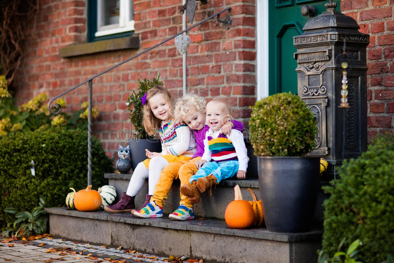 Kids at house porch on autumn day. Group of little children sitting on stone stairs to the house door on warm autumn day during Halloween or Thanksgiving time royalty free stock photography