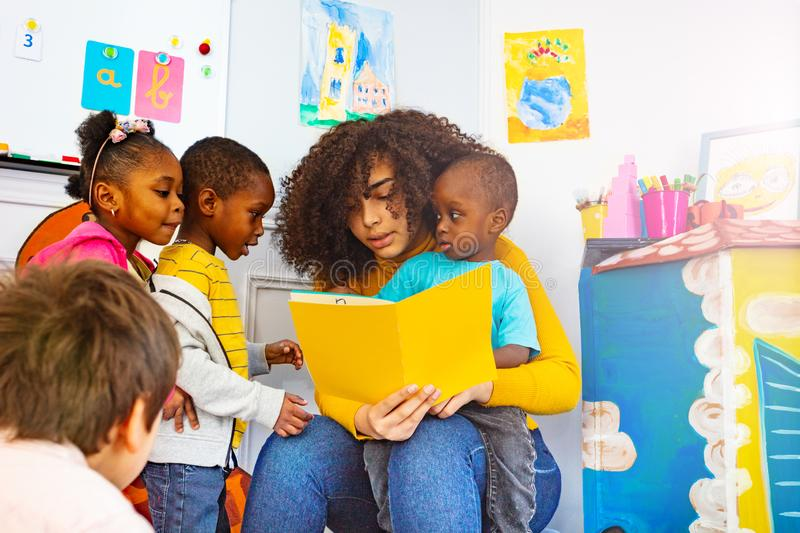 Group of little kids listen to teacher read story. Group of little kids listen to teacher reading a story standing around in nursery class stock images