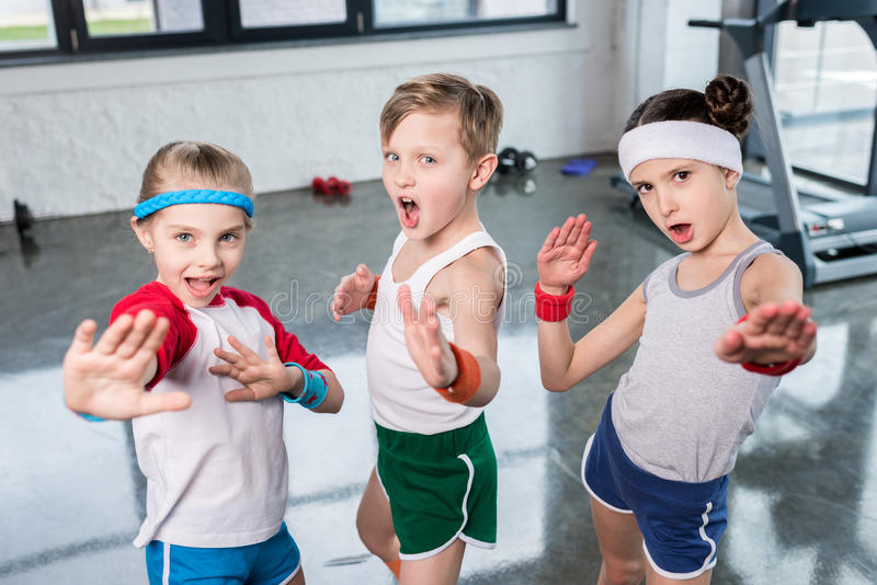 Group of little kids in sportswear exercising and posing at camera in gym. Children sport school concept royalty free stock photography