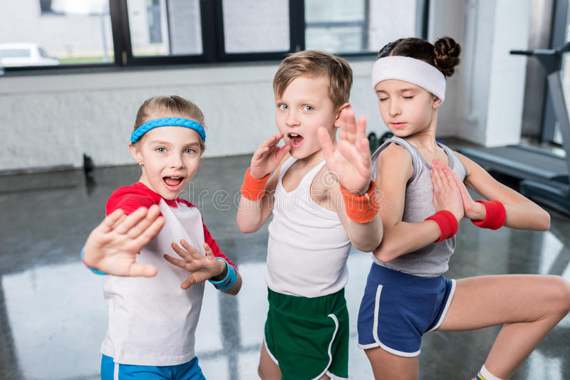 Group of little kids in sportswear exercising and posing at camera in gym. Children sport school concept stock photo