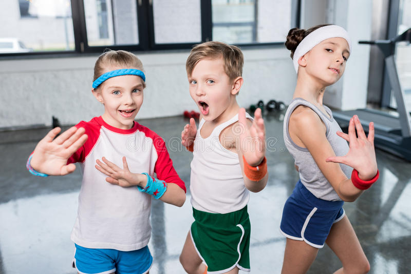 Group of little kids in sportswear exercising and posing at camera in gym. Children sport school concept stock photos