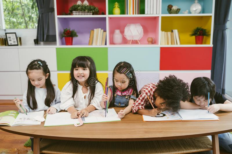 Group of little preschool kids drawing paper with color pencils . portrait of children friends education concept. stock image