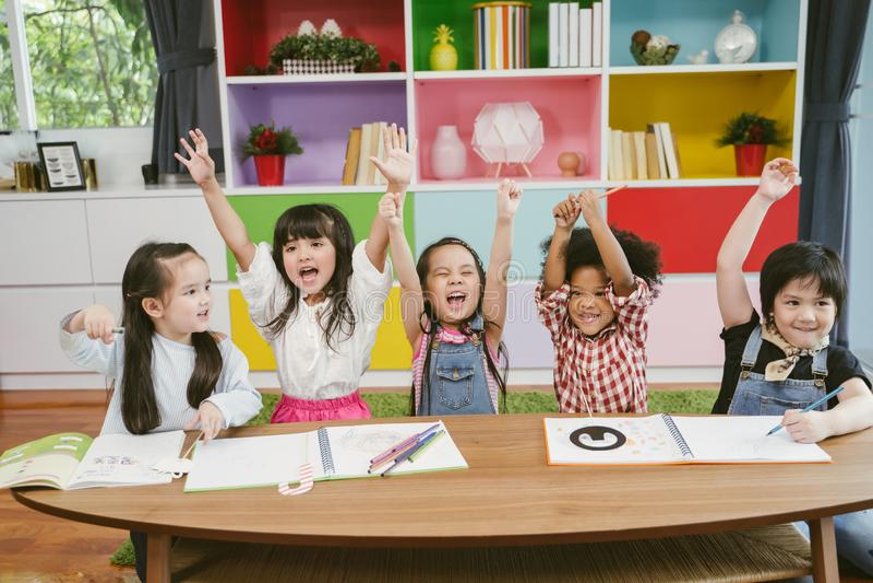 Group of little preschool kids hands up in class . portrait of children diversity education concept. stock photo