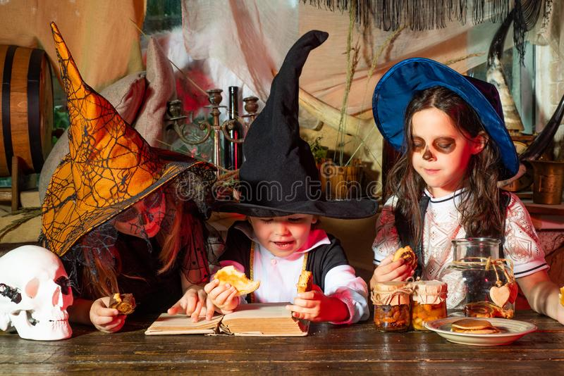Group of little witch with a pumpkin and sweets. Surprised group little zombie in Halloween costume eating treat - stock images
