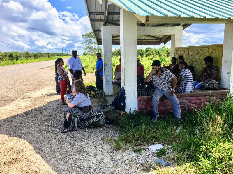A group of locals and one tourist waiting at a remote bus stop for the local bus heading to Placencia along the side of the highwa royalty free stock image