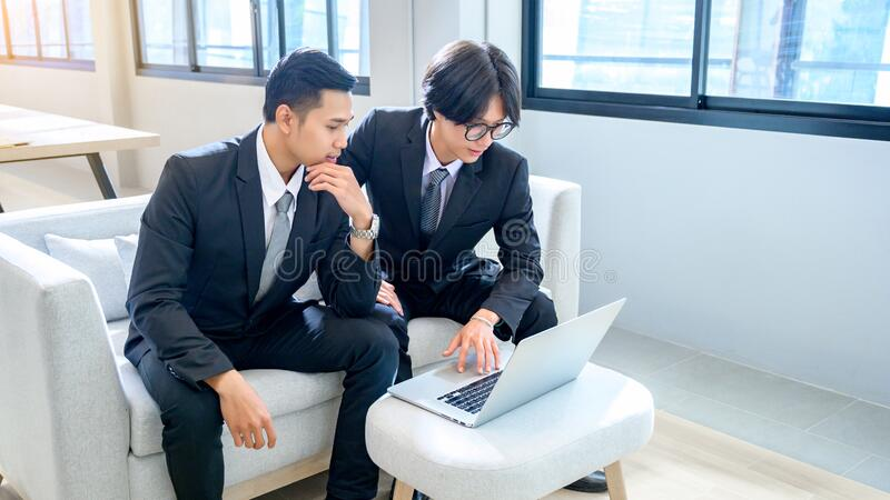 A group of 2 male business men are working with computers seriously in the office. A group of 2 male business  men are working with computers seriously in the stock photo
