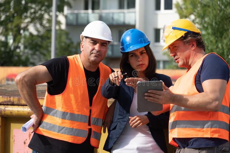 Group of male and female workers on construction site stock images