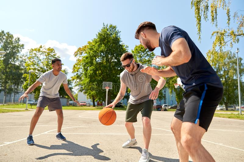 Group of male friends playing street basketball royalty free stock image