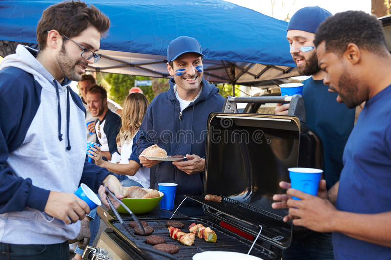 Group Of Male Sports Fans Tailgating In Stadium Car Park stock images